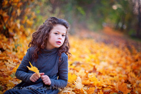 Girl in fall leaves